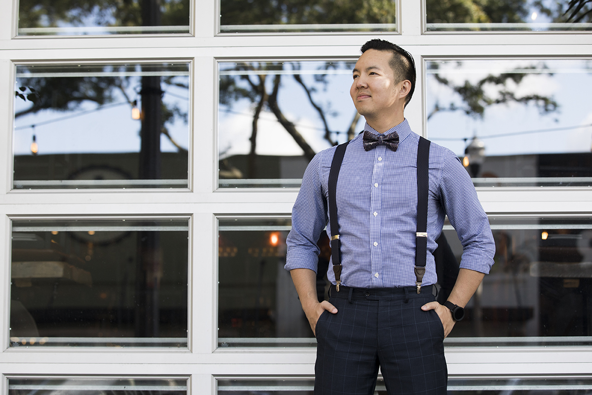 A man dressed in a bow tie, suspenders and a dress shirt stands in the shade.
