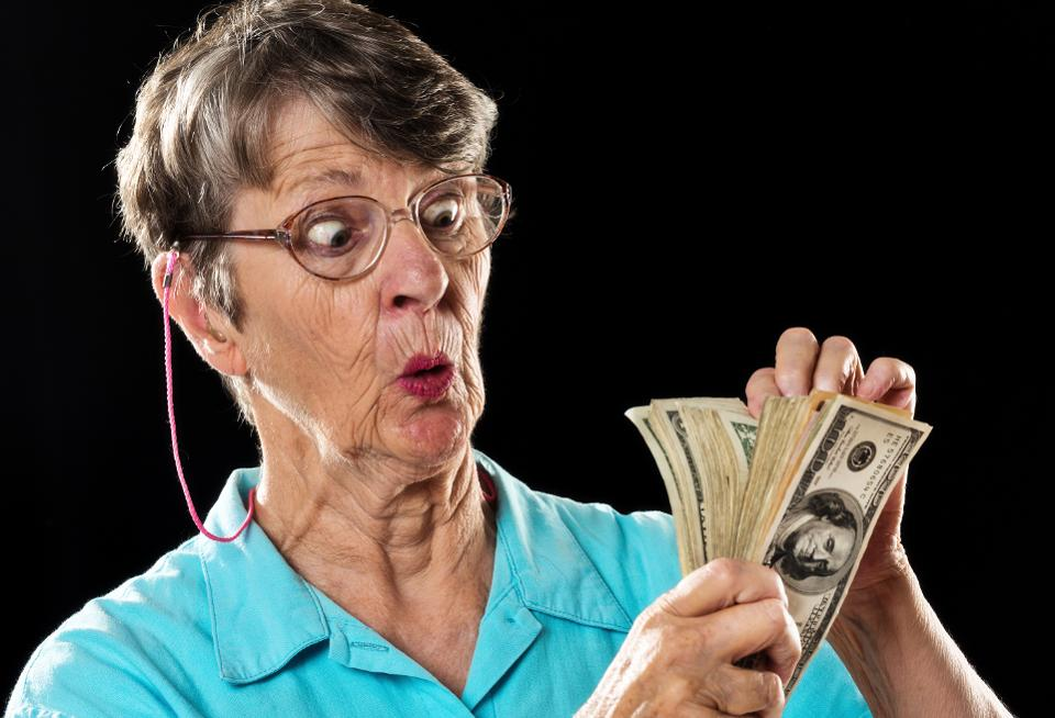 Amazed old woman counting thick sheaf of dollars, wide eyed