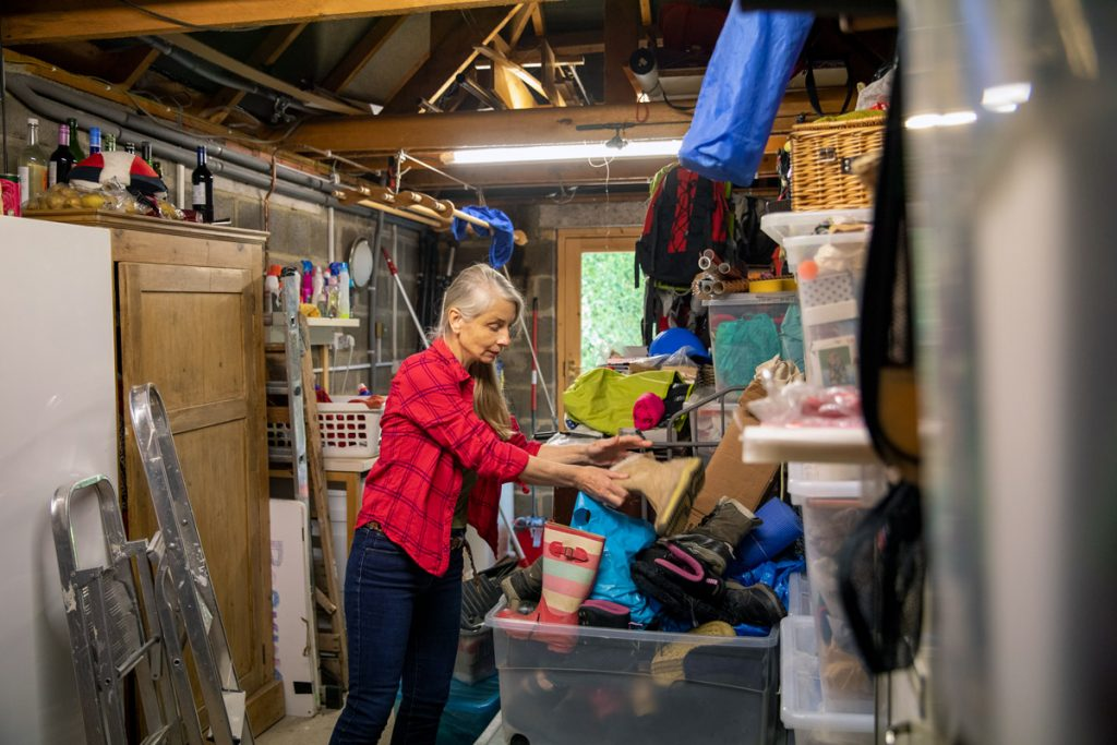 A woman cleans out her garage. One way to make money in retirement is to look at your empty nest and see if there's anything you can sell.