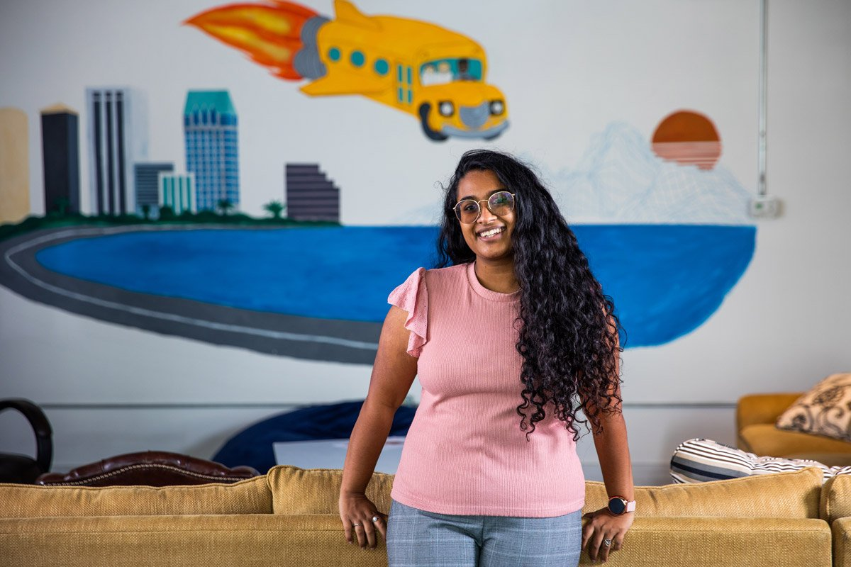 This is a portrait of a woman who finds tutoring gigs through the Knack app. She has long curly dark hair. Behind her is a painting of the magic school bus.