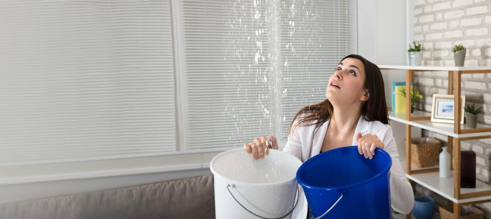 Woman Holding The Buckets Under The Water Leakage