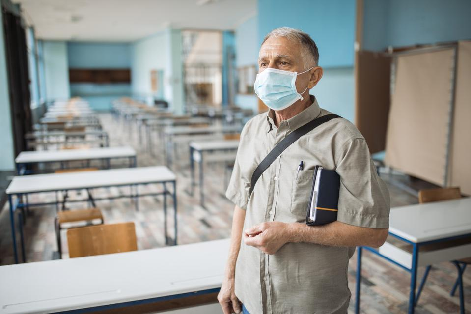 Portrait of professor in an empty classroom with face mask