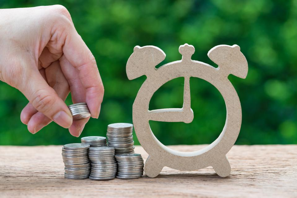 Woman hand holding stack of coins money putting on stack of coins and wooden alarm clock as long term investment timeline or savings concept
