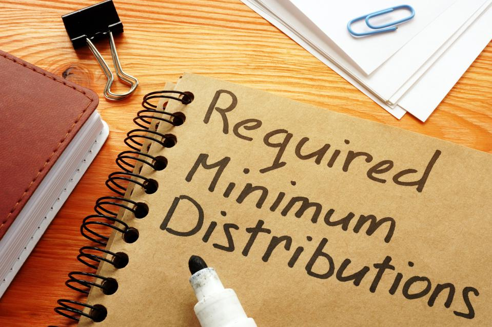 ″Required minimum distributions″ phrase written in marker on cover of a spiral notebook.