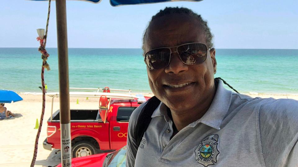 A Black Firefighter standing in front of his fire truck on the beach in Miami, Florida.