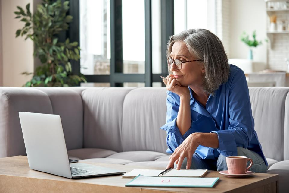 Senior mature older woman watching business training, online webinar on laptop computer remote working or social distance learning from home. 60s businesswoman video conference calling in virtual chat