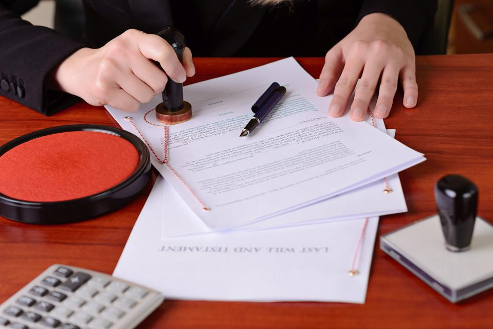 Notary's public hands stamping the testament and last will