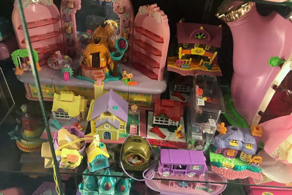 Polly Pockets sit in a glass case.