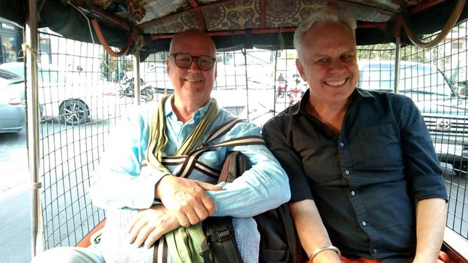 Two business owners riding in a tuk-tuk.